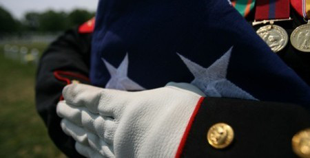 "A folded national ensign is held carefully prior to the burial of Maj. Douglas A. Zembiec, former commander of E Company, 2nd Battalion, 1st Marine Regiment.  Zembiec was killed in action May 10.  He once told reporters during combat in Fallujah his Marines ""fought like lions.""  Zembiec was laid to rest by the Marine with whom he served May 15."